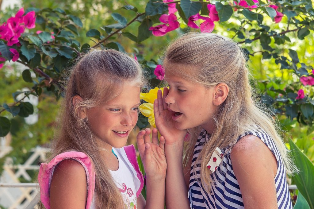 A girl wispering in her sisters ear to warn her of what happens when you run away from your problems