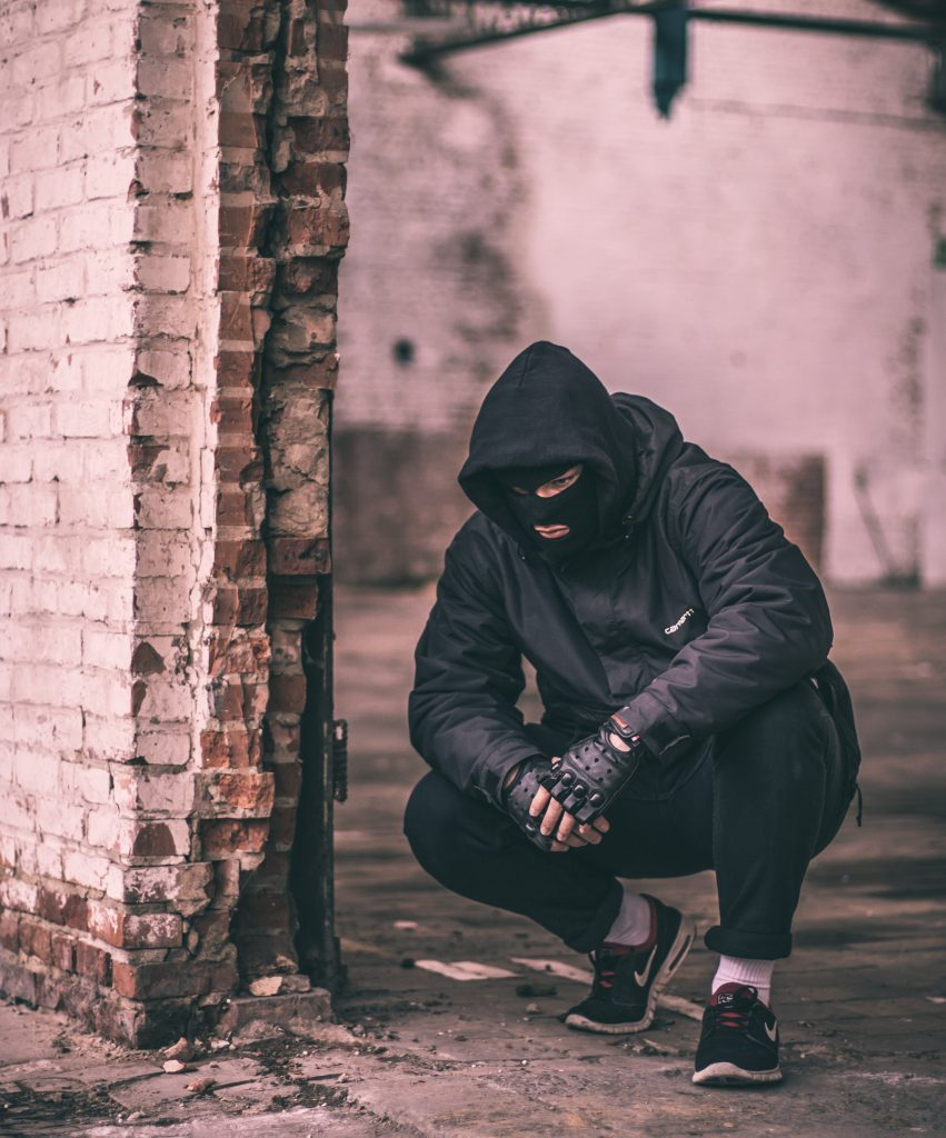 Man with a balaclava mask kneeling down to show a fugitive in hiding and what happens when you run away from your problems