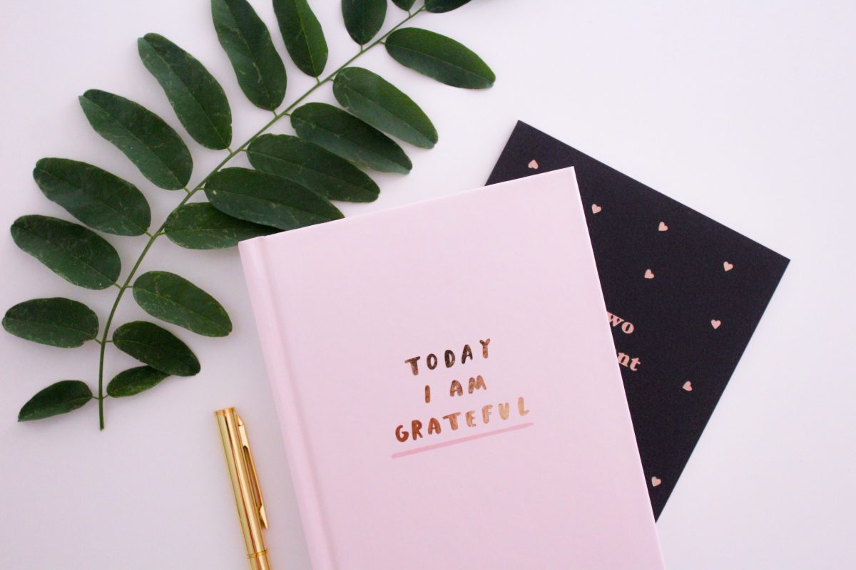 A notebook with a pen and leaf next to it with the words today I am grateful to show how you can be more grateful and positive