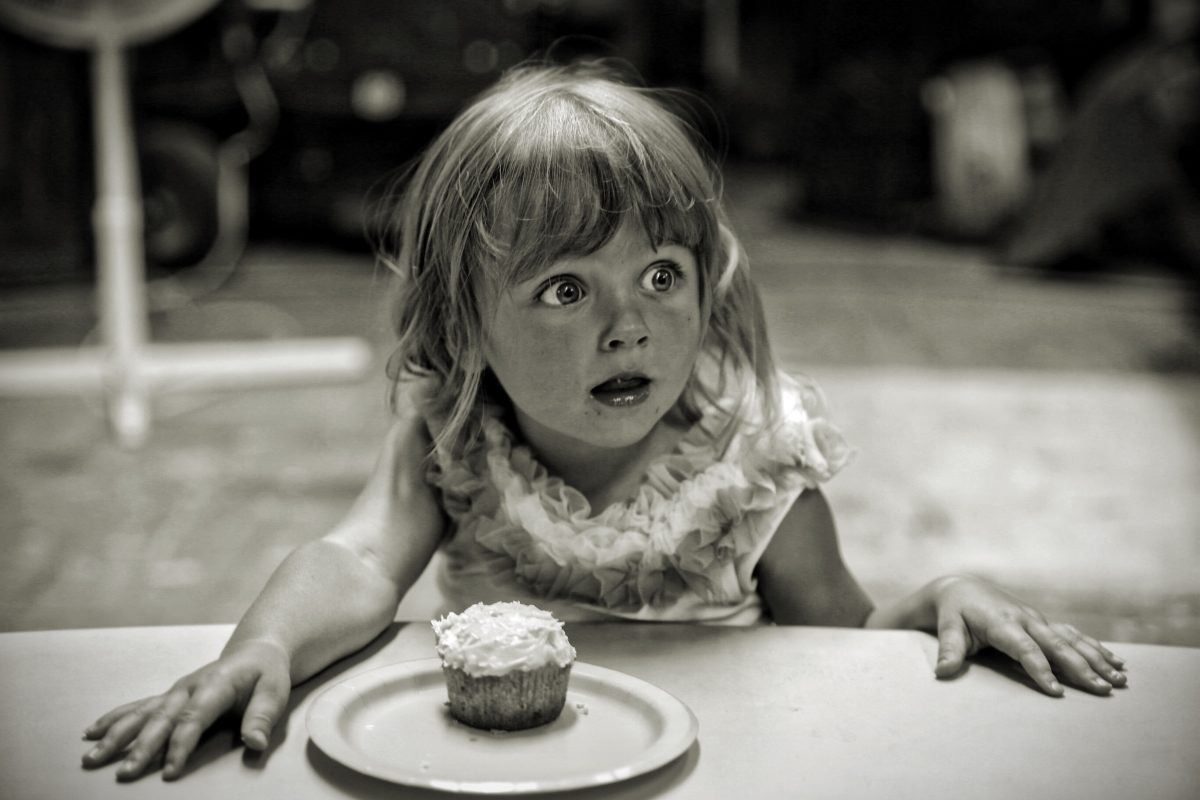 A black and white photo of a little girl sitting at a table with a cupcake in front of her suprised at the answer to how can I overcome my fear of change