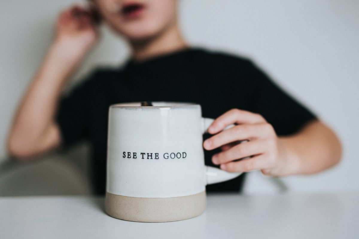 Boy with his hand on a mug that says see the good to show how can I overcome my fear of change