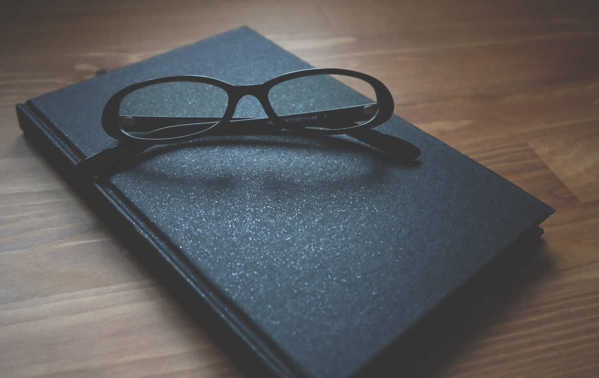 A notebook with a pair of eye glasses ontop to show the act of seeing a therapist