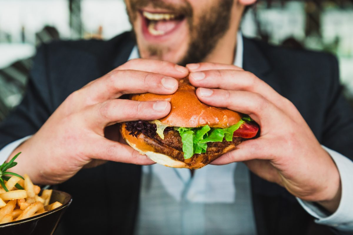 A man about to dig into an unhealthy burger to make himself feel good.
